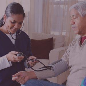 Nurse checking elderly man's blood pressure