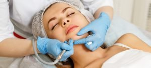 woman receiving a dermabrasion procedure from a dermatologist to remove acne scars