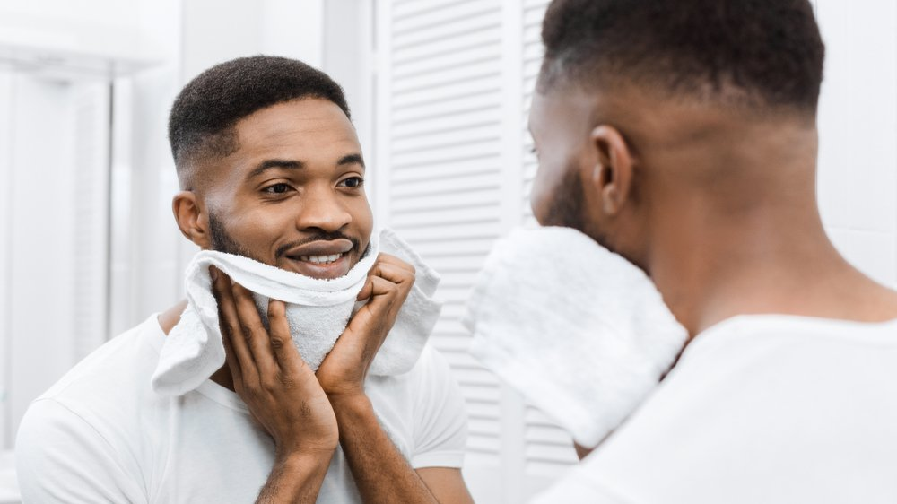 man patting his face dry with a towel while looking in the mirror