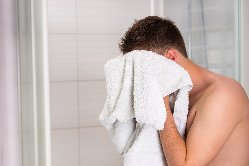 man drying his face with a towel
