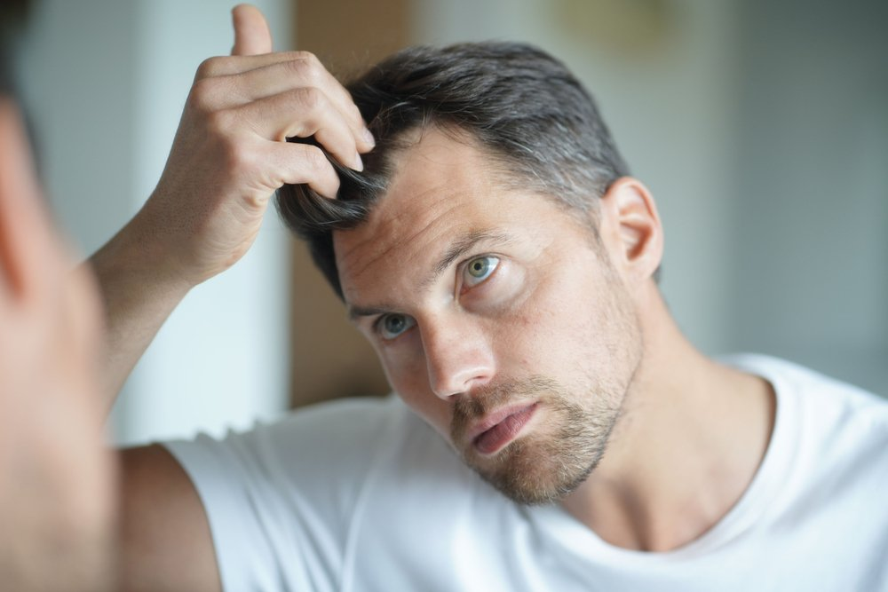 man looking in the mirror at his receding hair line