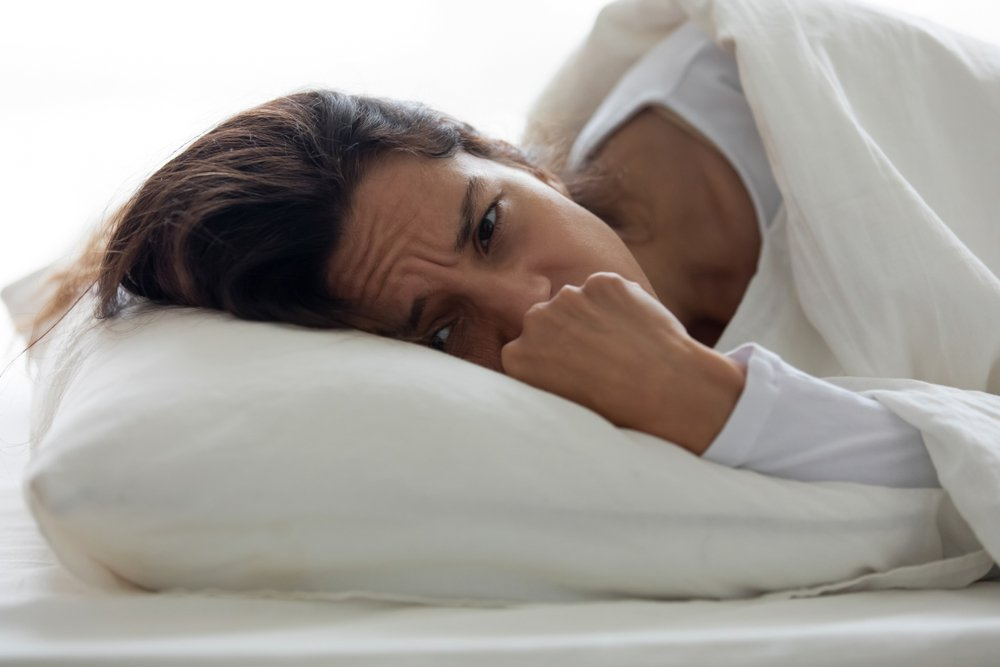 woman laying awake on bed