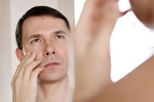 man examining his skin in a mirror