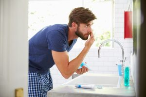 man applying skin care product to his face in the mirror