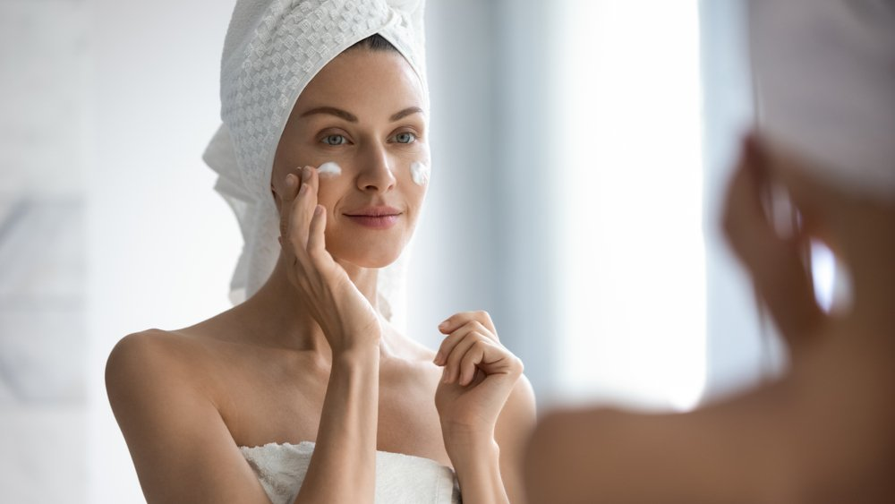 woman apply a facial cream while wearing a towel on her head and looking in the mirror