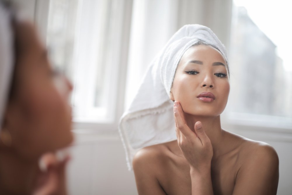 woman wearing a towel on her head running her fingers over her jaw while looking in the mirror