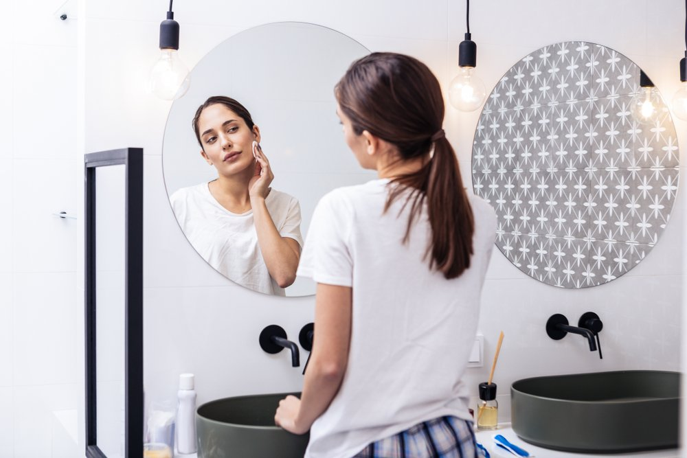 woman wearing pajamas dabbing her face with a cleansing pad while looking in the mirror