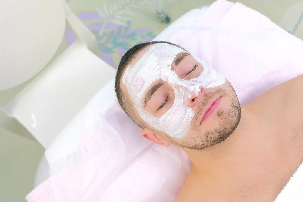 man lying down peacefully with facial mask while taking care of his skin