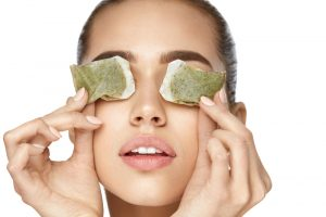 woman treating dark circles with tea bags over her eyes