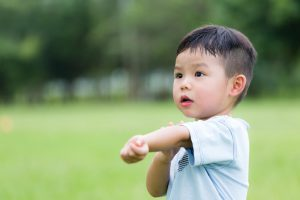 little boy scratching his arm