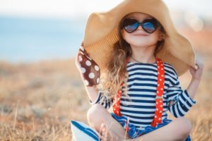 Little girl wearing hat and sunglasses for UV protection