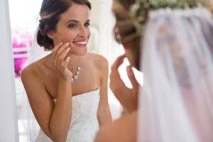 Bride looking at her face in the mirror