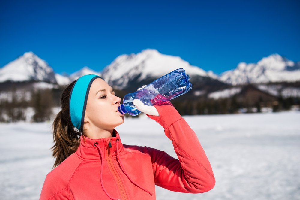 woman in winter coat drinking from water bottle in the mountain