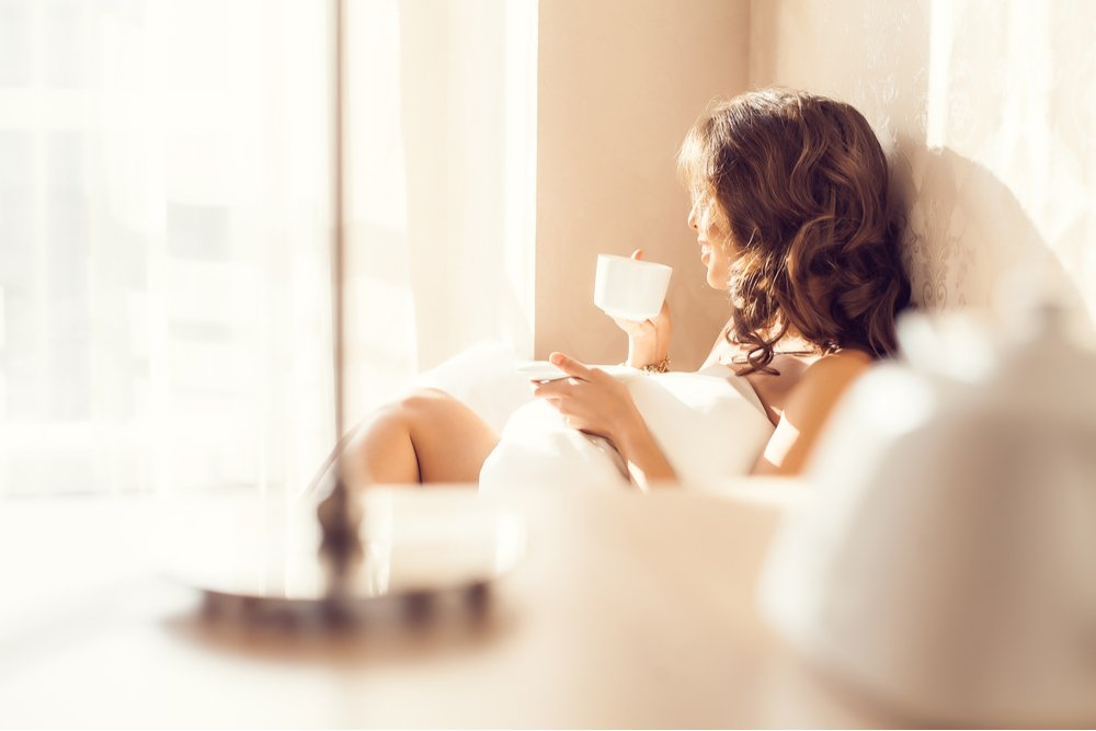 woman sitting on the couch inside with a drink in her hand